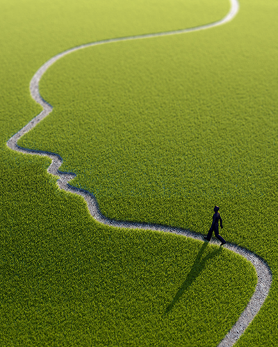 Stylised green field with a path in the shape of a face with a person walking along it