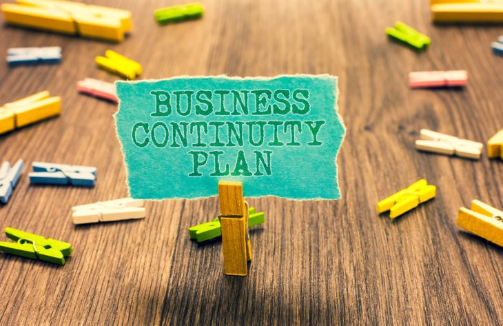 Piece of tirn blue paper held with a small peg. Writing on the paper says Business Continuity Plan